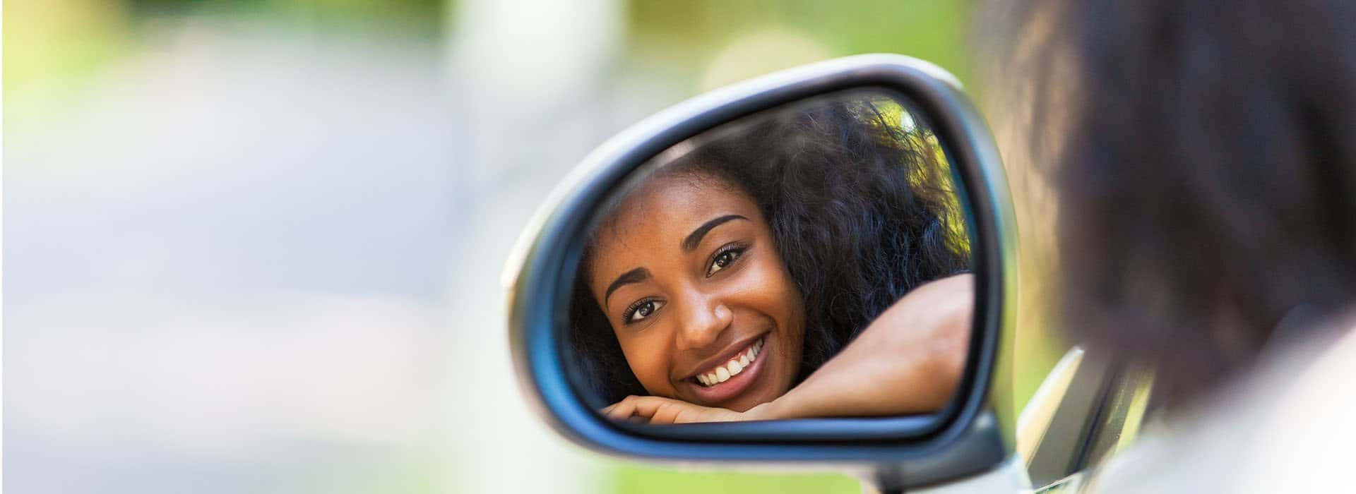Zimnat young lady looking in rearview mirror